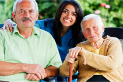 happy caregiver with two elderly