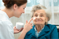 elderly woman getting a cream on her face