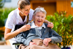 elderly woman in a wheelchair is smiling